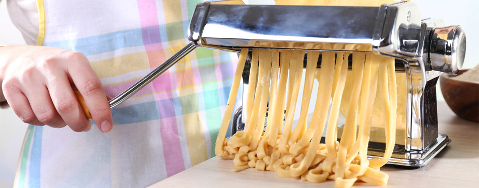 woman making pasta with pasta maker