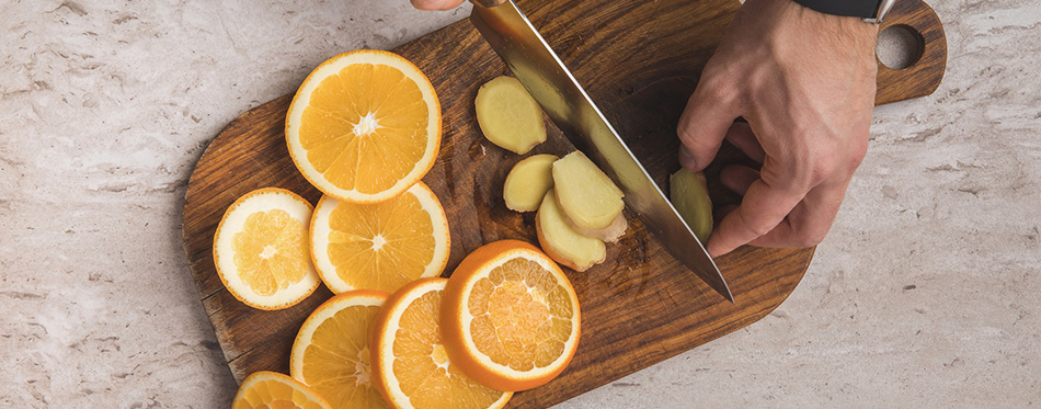 man cutting ginger on wooden board