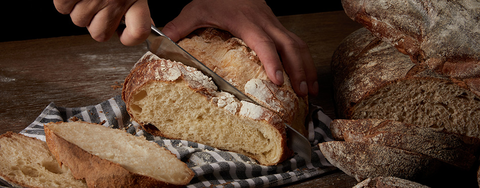 male baker cutting bread by knife