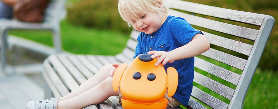 Adorable little boy sitting on the bench with lunchbox