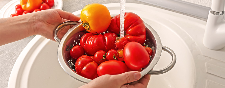 Hands washing tomatoes in colander