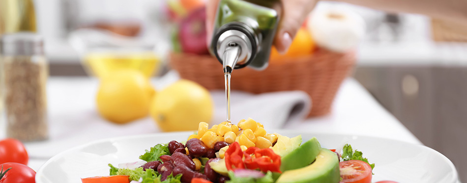 Woman pouring olive oil onto fresh salad