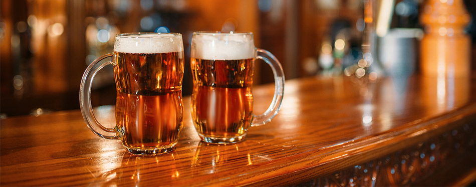 Two beer mugs on wooden bar