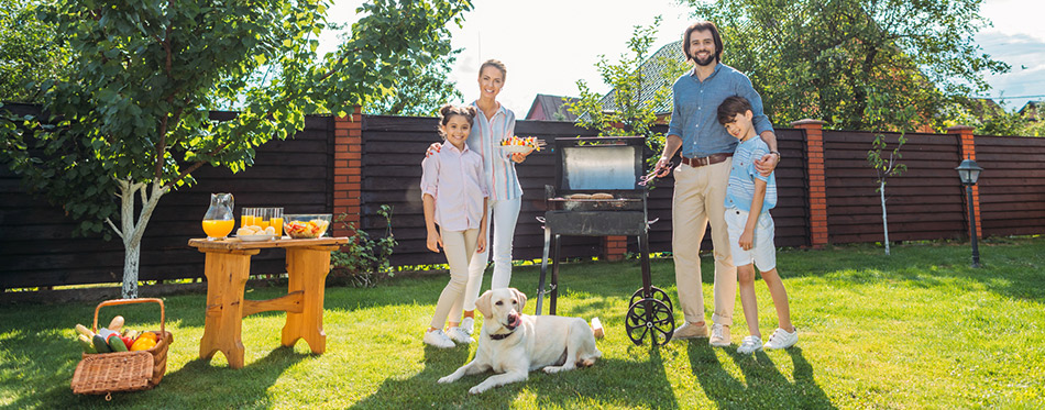 Family with dog having barbecue