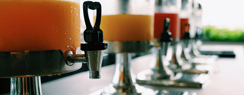 Selective focus at heart valve shape of juice dispenser on the table