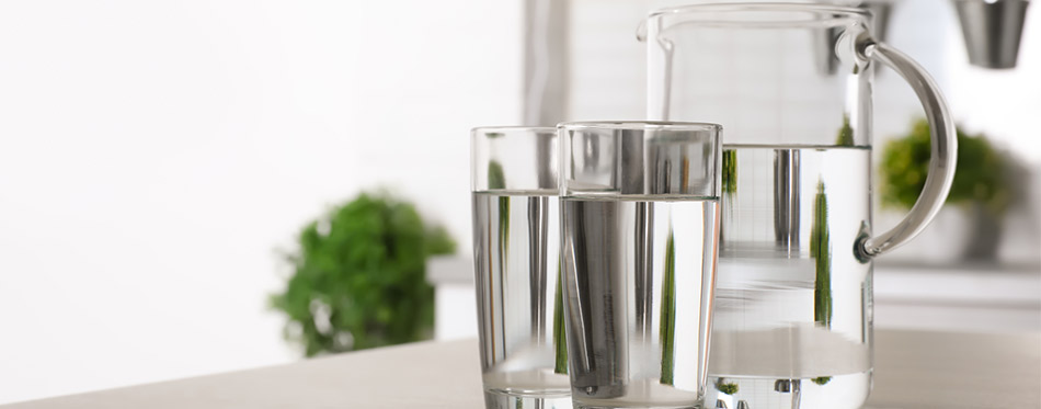 Glassware of fresh water on table indoors.