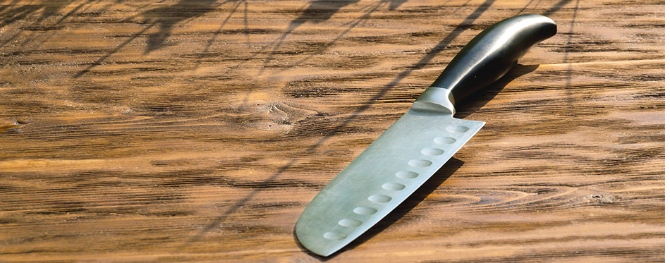 The knife lies on the old wooden surface. Knife Santoku.