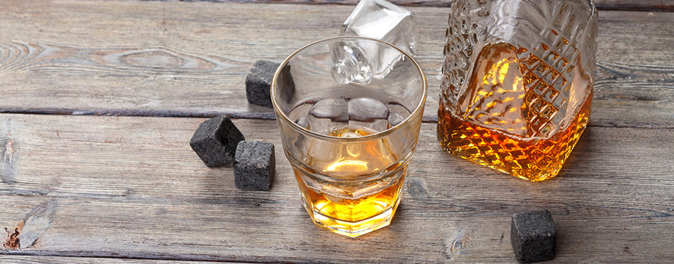 Whiskey beverage in glass with stone