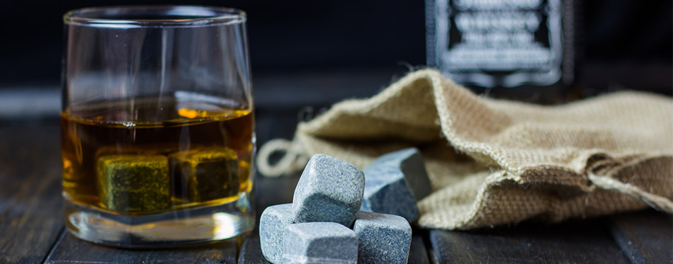 Whiskey in a glass with stones for cooling drinks on a wooden table