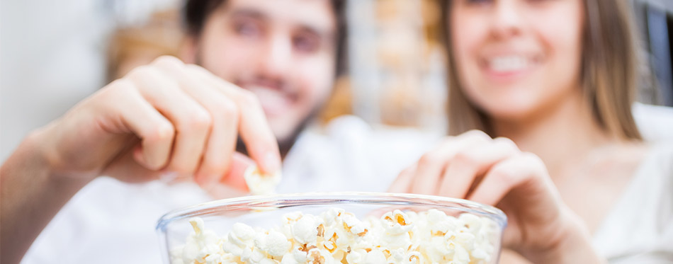 Couple eating popcorn while watching a movie