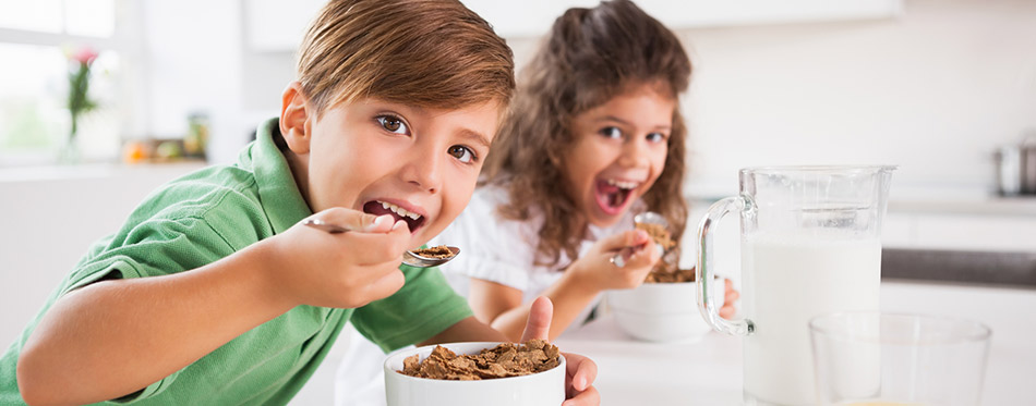 Two children looking at camera while eating cereal