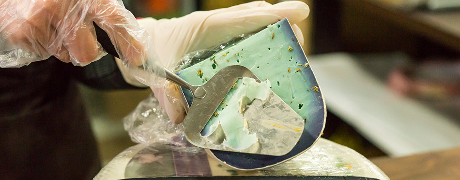 Person shaving cheese with a blade slicer
