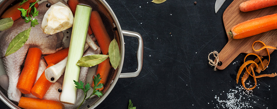Preparing chicken stock with vegetables in a pot