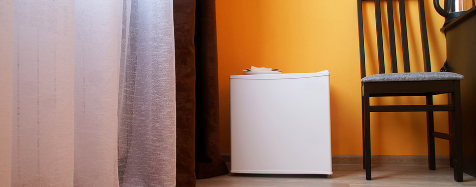 Small compact white refrigerator in the interior of a cramped st