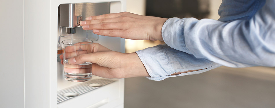 Woman filling glass from a water dispenser