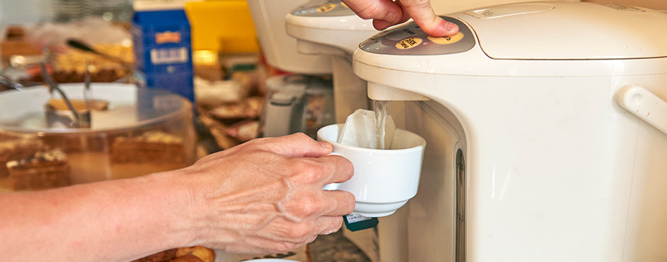 Woman pouring water from the hot water dispenser